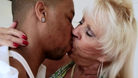 A blonde granny is receiving a large black pecker on the bed
